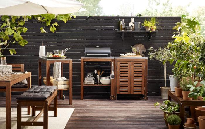 Ikea Äpplarö utemöbelserie med grill i brunt massivt trä.