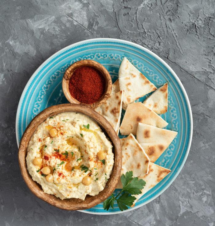 Hummus och bröd på fat.